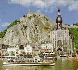 Gezicht op Dinant. Dinant is een echt toeristenstadje waar u een terrasje kunt pikken, over de boulevard flaneren of een restaurantje opzoeken. Op de voorgrond de Maas, hier varen rondvaartboten voor een kleine tocht, maar richting Frankrijk of naar de stad Namen is ook mogelijk.