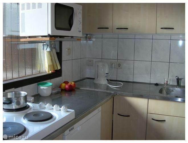 De complete keuken. Deze bevindt zich links van de ingang. U ziet de magnetron, waterkoker en elektrische kookplaten, de koelkast en rechts nog net de spoelbak. Er is ook een koffiezetapparaat en de kastjes bevatten pannen, serviesgoed en bestek.