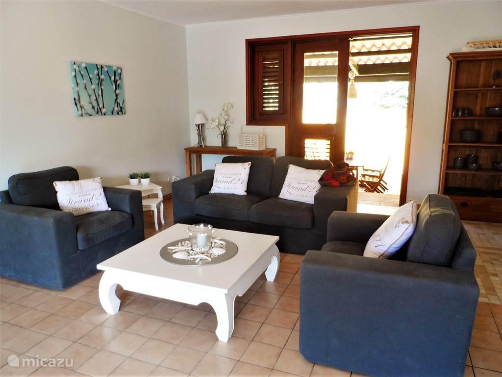 Woonkamer voorzien van comfortabele stoelen en bank. Door de ligging van het huis op de wind heeft u een constante bries door de woonkamer.