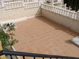 ruim terras met toeganggsdeur naar de kelderruimte(berging voor tuin meubels en parasol)