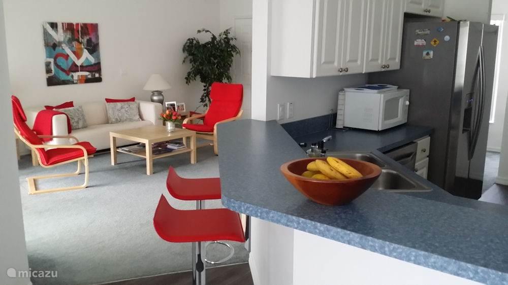 Doorkijk via de keuken naar de woonkamer. Mocht het buiten 's ochtens aan de frisse kant zijn (en dat komt wel eens voor in de wintermaanden) dan kan het ontbijt binnen aan de bar worden genuttigd.