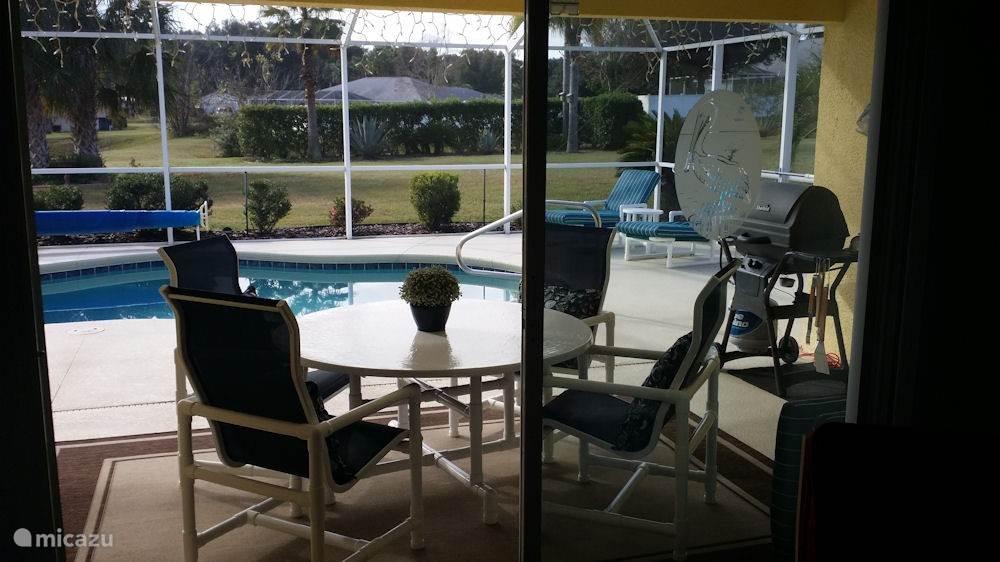 Blik vanuit de woonkamer naar het terras en het zwembad. In het overdekte gedeelte van het terras staat een gezellig zitje om even in de schaduw te kunnen zitten.