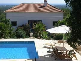 Het verkoelende zwembad met uitzicht naar het huis en de zee. Vanuit elke kamer is er makkelijk toegang naar de tropische achtertuin met het zwembad. Volop schaduw door de parasollen.