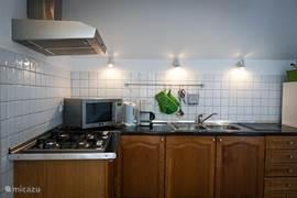 Penthouse appartement: volledig ingerichte keuken met oven/magnetron, 4-pits kookplaat, afzuigkap, koelkast, koffiezetapparaat, waterkoker, broodrooster, pannen, borden, bestek en alle overige kookbenodigdheden.