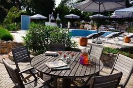 In de tuin zijn diverse terrassen. Lekker in de zon bij het zwembad, in de schaduw onder de olijvenboom...