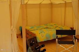 The room is square, and the whole tent has a wooden floor, with the back of the tent, two sleeping areas are situated.