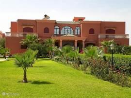 aanzicht van de villa met een mooi grasveld