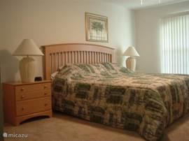 De ouderslaapkamer heeft een lekker groot king size bed met twee nachtkastjes.