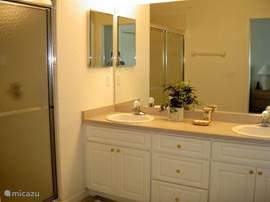De grote badkamer bij de ouderslaapkamer heeft een douche en twee wastafels.