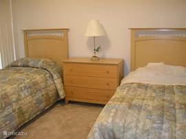 De slaapkamer met twee eenpersoonsbedden is voorzien van een 22' LCD TV