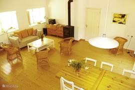 ruime woonkamer met zithoek, eetgedeelte en houtkachel en openslaande deuren naar terras