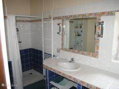 Bathroom on ground floor with large shower and washbasin with shelf for changing babies.