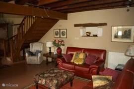 Zithoek onder de mezzanine met twee leren banken en fauteuils.