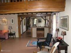 woonkamer gezien vanaf de haardpartij. U ziet nog net een stukje van de mezzanine alwaar 2 banken en 6 fauteuils + tafels staan.