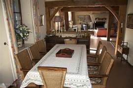 De eethoek met tafel voor 8 personen met doorkijk naar de woonkamer. Voor meer personen kan er  voor extra tafels en stoelen worden gezorgd die onder de mezzanine gezet worden voor een 18 persoons eetkamer.