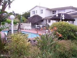 villa en zwembad gezien vanuit de tuin