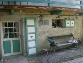Een zitje bij de kelder met uitzicht op de straat en het gezellige terras van Restaurant Le Roitelet aan de overkant van de straat.
