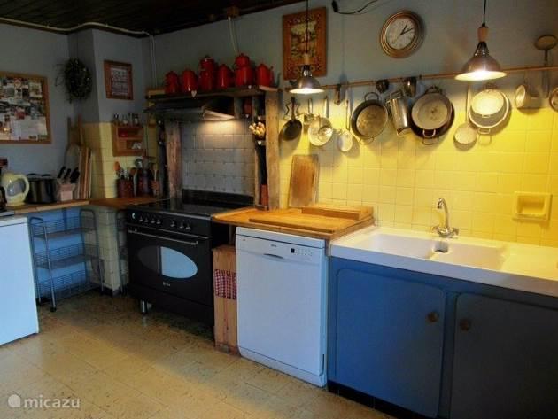 Een gedeelte van de keuken met groot fornuis met oven, 2 ijskasten, afwasmachine, dubbele koffiezetter, magnetron, waterkoker, toaster, bakblikken enz.