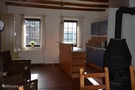 Woonkeuken in Huis Abertamy, met grote eetkamertafel, keuken (2005) en gezellige houtkachel
