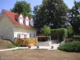 Woning zijkant met terras, hetgeen nog niet op de hooffoto te zien is. Het terras is in 2011 geplaatst.