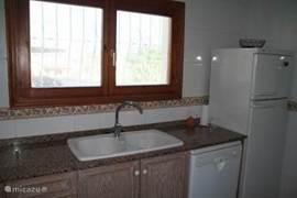 Dubbele spoelbak, vaatwasmachine en een grote koelkast voor voldoende frisse drankjes.