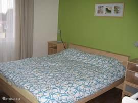 Slaapkamer met een tweepersoons bed, en een kinderbedje.