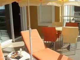 Het grote L-vormig terras is bereikbaar via de voordeur of via de schuifpui vanuit de woonkamer.