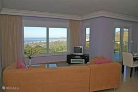 De sfeervol ingerichte <b>woonkamer</b> biedt een prachtig uitzicht!