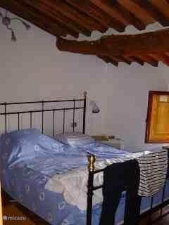 Slaapkamer voorzijde. Ook in de slaapkamers is de traditionele bouw gehandhaafd met een mooie terracotta vloer en een traditioneel balkenplafond.