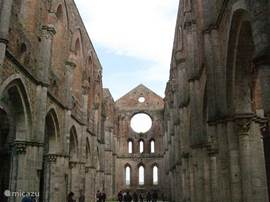 De abdij zonder dak in San Galgano. Vlakbij is ook het zwaard in de rots, dat de latere heilige er volgens de legende in stak toen hij zich bekeerde en later door niemand meer uit de rots getrokken kon worden.