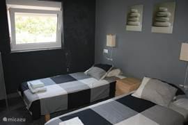 Slaapkamer met twee eenpersoonsbedden.