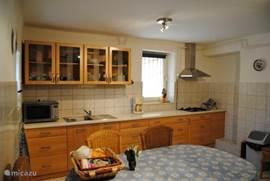 Grote woonkeuken, zeer compleet ingericht: gaskookplaat met afzuigkap, combi magnetron-oven, combi koelkast/diepvries, veel servies en glazen, bestek, koffiezetter, waterkoker, gourmetstel.