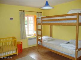 bright, spacious children's room with bunk beds and baby bed.