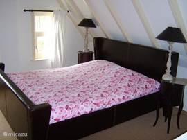 Slaapkamer met groot 2-persoonsbed.