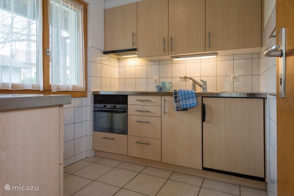 De efficiënt ingerichte keuken met voldoende bergruimte, keramische 4-zonekookplaat, afzuigkap, heteluchtoven, koelkast met vriesvak en compleet serviesgoed voor 6 personen.