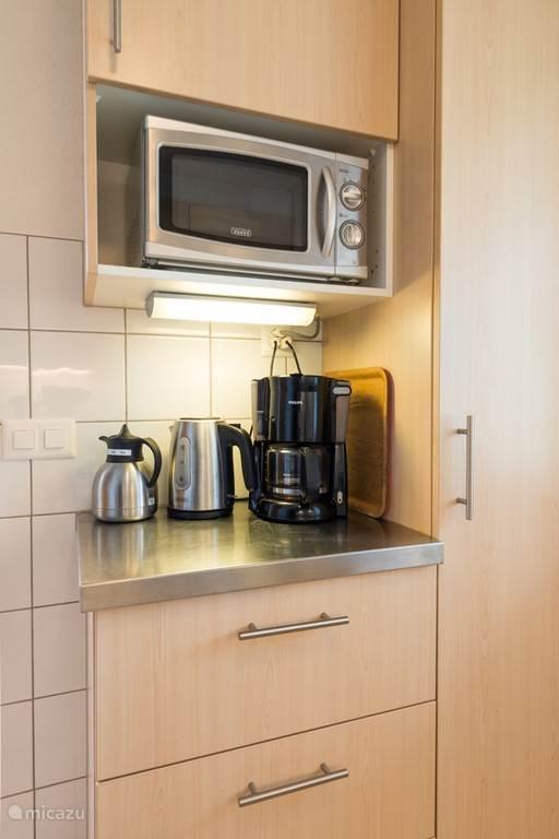 De coffee-corner met warmwaterkoker, isoleertheekan en magnetron.