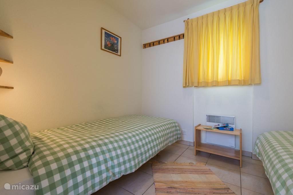 De kleine slaapkamer heeft aan weerszijden een 1-persoonsbed van 80x200, bedeleeslampje en afzetvlak boven het bed.