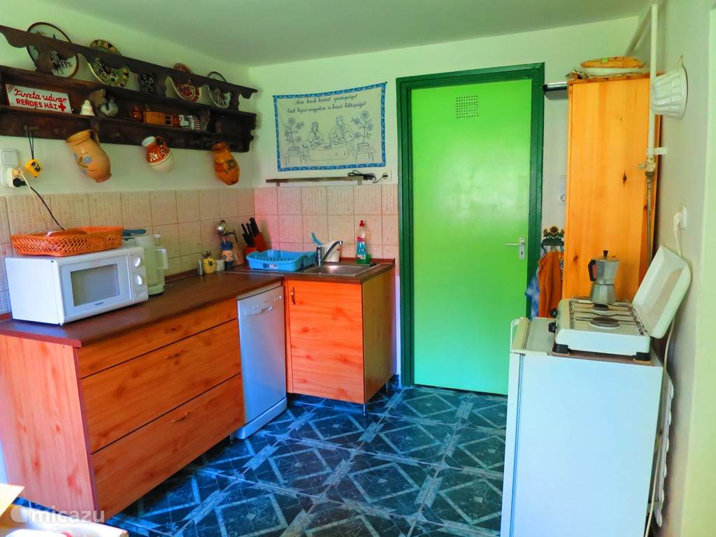 Cozy kitchen with dishwasher, microwave, refrigerator and two burner stove. Plates, cutlery, pans etc are naturally present