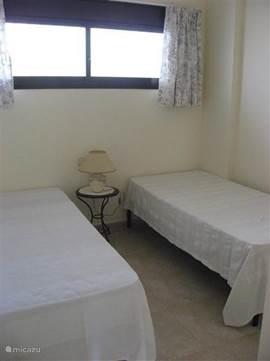Slaapkamer 2 met twee éénpersoonbedden en een ruime inbouwkast
