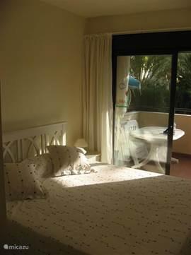 Hoofd slaapkamer met tweepersoonsbed, een ruime inbouw kast en een schuifpui naar het balkon/terras