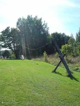 In de tuin staan verschillende speeltoestellen, zoals een zandbad, schommels, klimrek en kabelbaan.