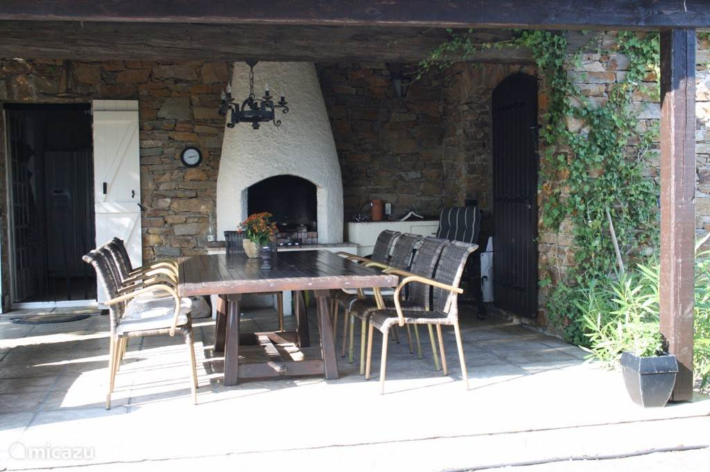 Overdekt terras met open keuken en barbecue.