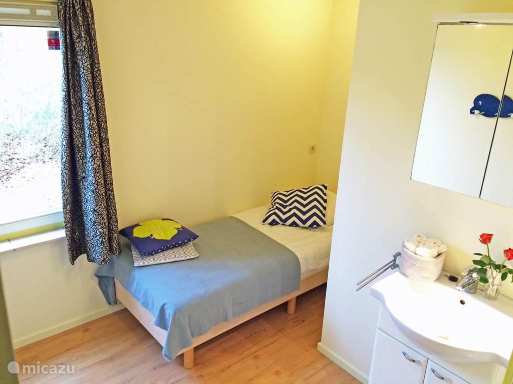 Ruime eenpersoonskamer met wastafel