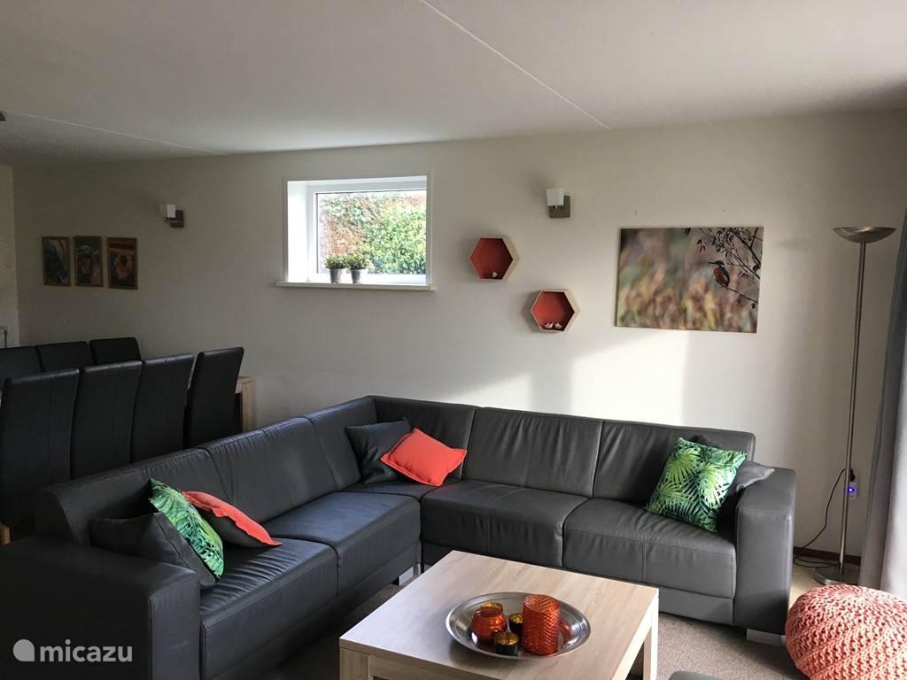Luxe woonkamer met loungebank, 2 leunstoelen, haard, flatscreen, dvd/stereoset en schuifpui op het zuiden.