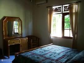 Dit is de slaapkamer op de begane grond, met tweepersoonsbed, kaptafel en een ruime kledingkast met leg- en hanggedeelte.