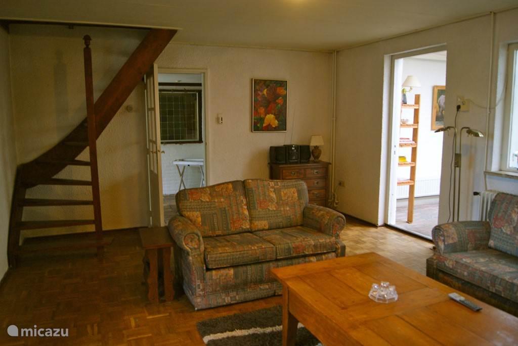 woonkamer met trap naar slaapkamer boven