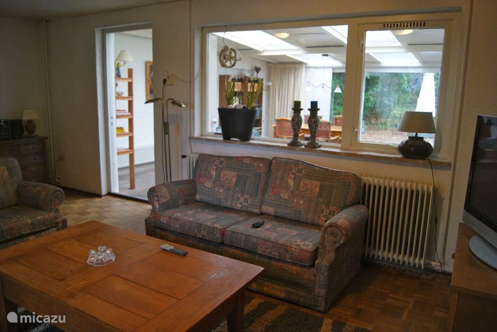 doorkijkje van woonkamer naar serre en tuin