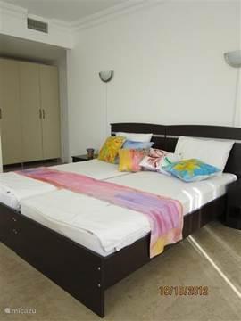 Een impressie van de slaapkamer met op het bed een handbeschilderde zijden loper en kussens. Deze tweepersoons slaapkamer heeft een eigen doucheruimte, toilet en wastafel. De slaapkamer geeft ook toegang tot het terras.