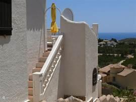 Van uit de zij tuin, kunt u via het trappetje naar het terras van de livingroom.