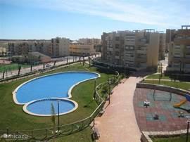 Uitzicht vanaf het terras van het appartement op het zwembad met kinderbadje